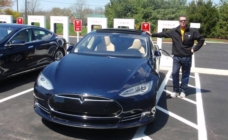 Ivon Lemire posant fièrement à côté de sa Tesla en charge à une Superborne (USA). MERCI POUR LE VIDÉO IVON!